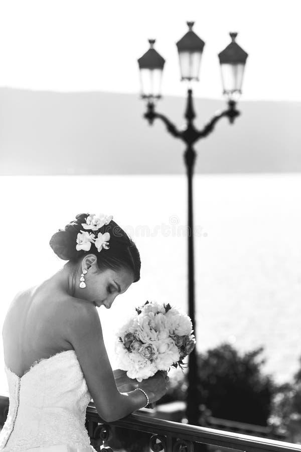 Emotionell sexig brunettbrud i den vita klänningen som poserar på balkong n arkivbild