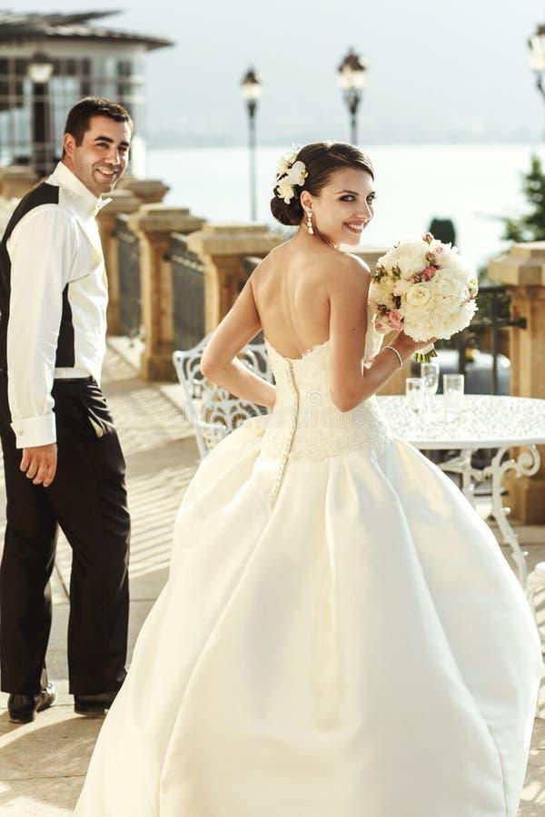 Emotionell sexig brunettbrud i den vita klänningen som poserar på balkong n arkivbilder