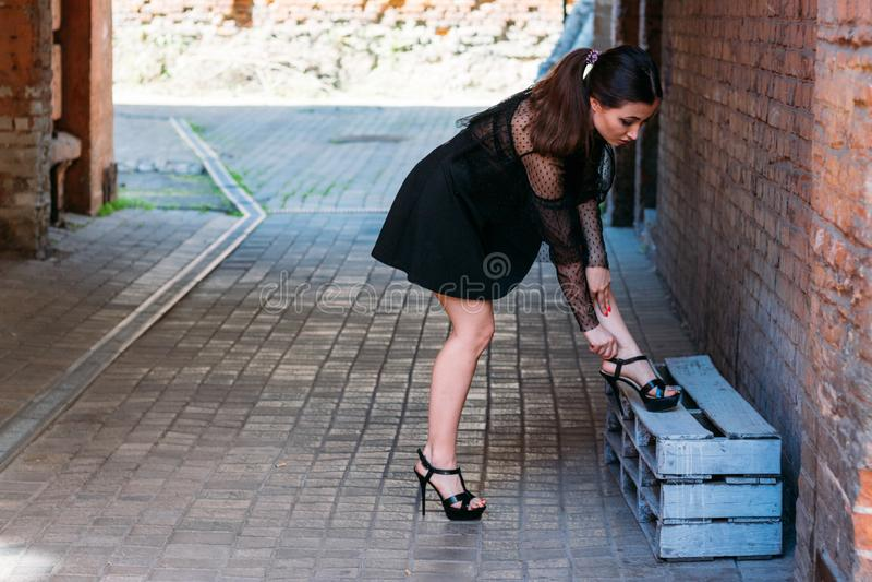 Emotionell stående av den stilfulla ståenden för mode av den nätta unga kvinnan stadsstående flickan justerar hennes skor som böj arkivfoton