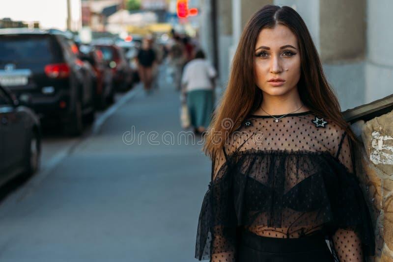 Emotionell stående av den stilfulla ståenden för mode av den nätta unga kvinnan stadsstående SAD flicka Brunett i en svart klänni arkivfoton