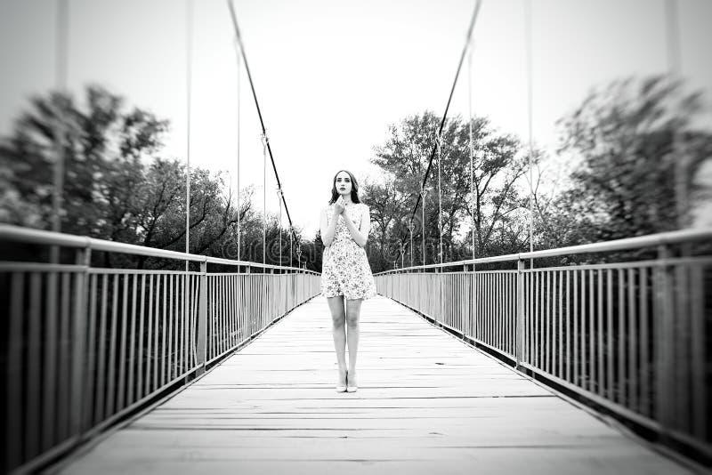 Emotionell stående av en flicka på en hängebro En flicka i en su arkivfoton