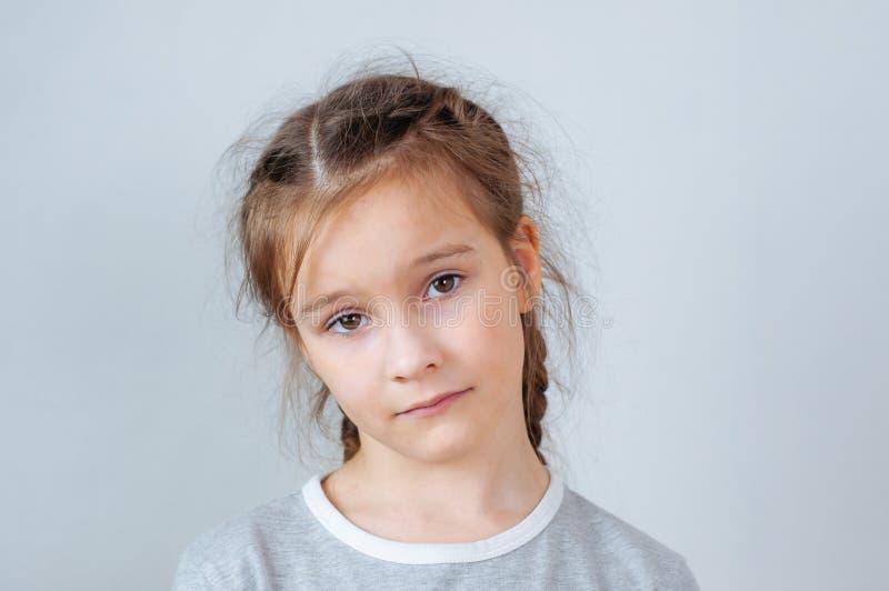 Emotionell st?ende f?r studio av en allvarlig liten flicka med l?ngt h?r royaltyfri foto