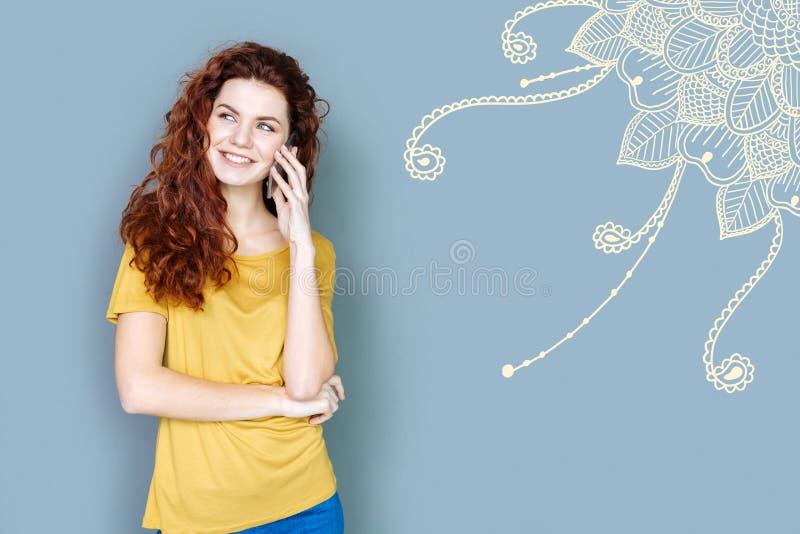 Emotionell student som ler, medan ha ett vänligt telefonsamtal royaltyfri bild