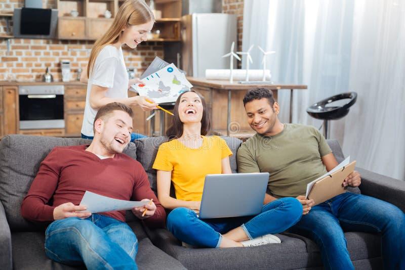 Emotionell student som rymmer en bärbar dator medan hennes vänner som nära sitter och skrattar royaltyfri bild