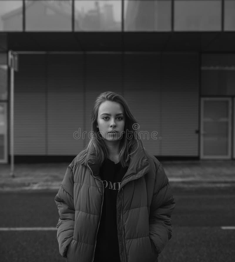 Emotionell svartvit stående av unga flickan i enormt omslag royaltyfria bilder