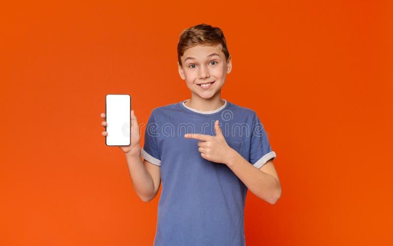 Emotionell tonårig pojke som pekar på den vita mobila skärmen och att le arkivbilder