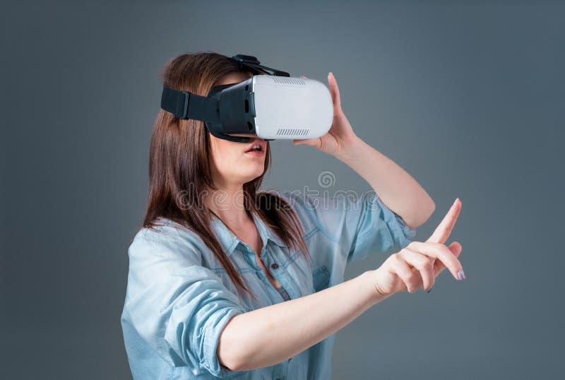 Emotionell ung kvinna som använder en VR-hörlurar med mikrofon och erfar virtuell verklighet på grå bakgrund royaltyfri foto