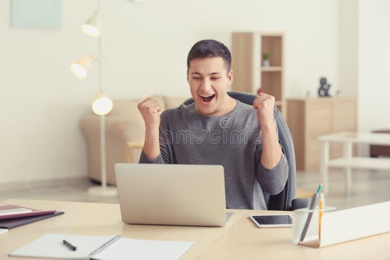 Emotionell ung man som arbetar med bärbara datorn i inrikesdepartementet royaltyfria foton