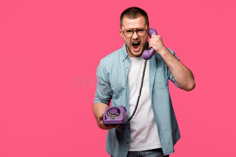emotionell ung man som skriker på telefonluren och ser den isolerade kameran arkivfoton