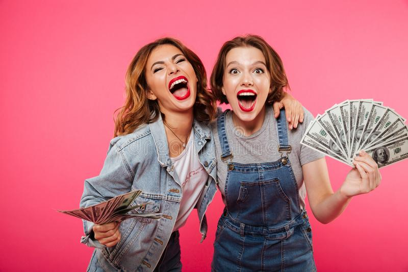 Emotionella nätta två kvinnavänner som rymmer pengar royaltyfria foton