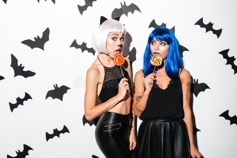 Emotionella unga kvinnor i halloween dräkter arkivfoton