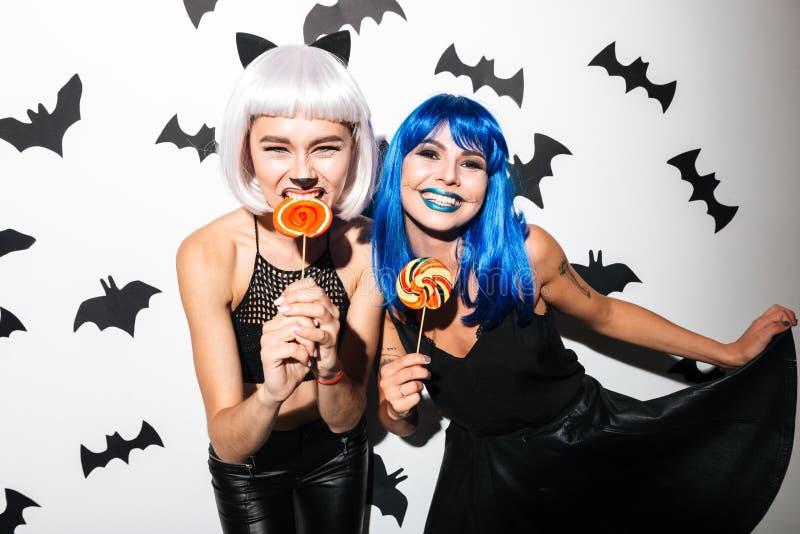 Emotionella unga kvinnor i halloween dräkter royaltyfri foto
