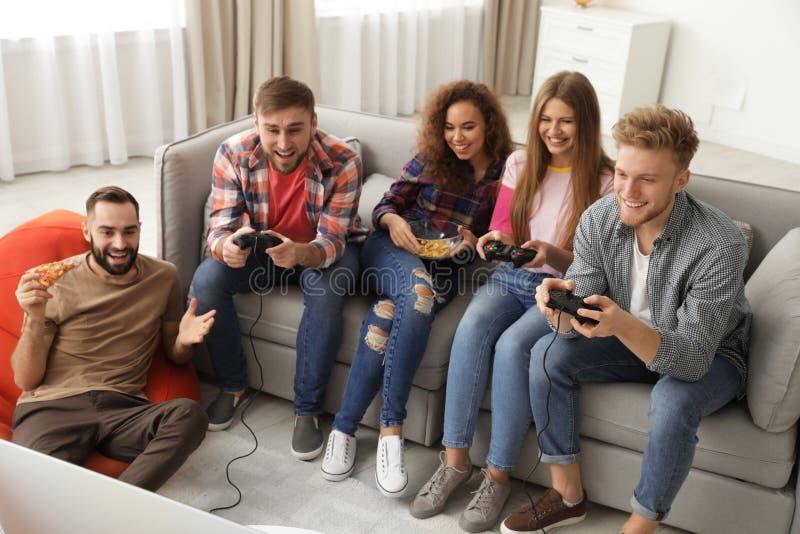Emotionella vänner som spelar videospel royaltyfria bilder