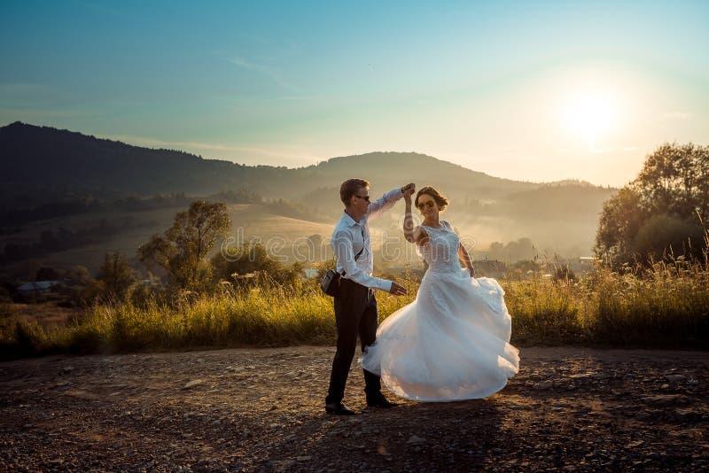 Emotionellt bröllopskott av den lyckliga dansen för glamournygift personpar på vägen under solnedgången härlig natursikt arkivbild