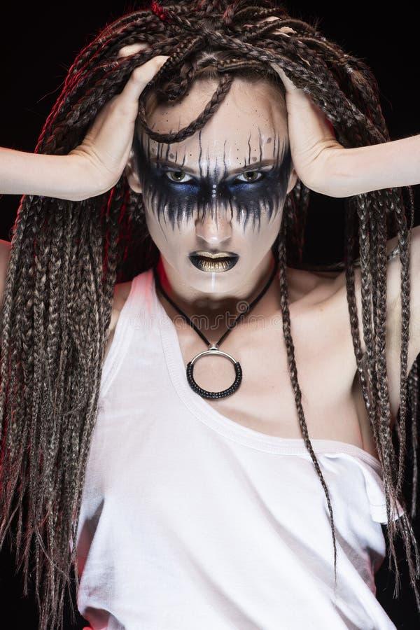 Emotionellt foto av en härlig ung slank flicka med idérikt smink och en frisyr av cornrows, bärande vit t-skjorta på en svart arkivbilder