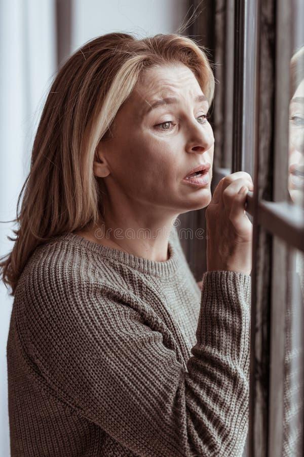 Emotionellt och ledset anseende för kvinnakänsla nära fönstret royaltyfri bild
