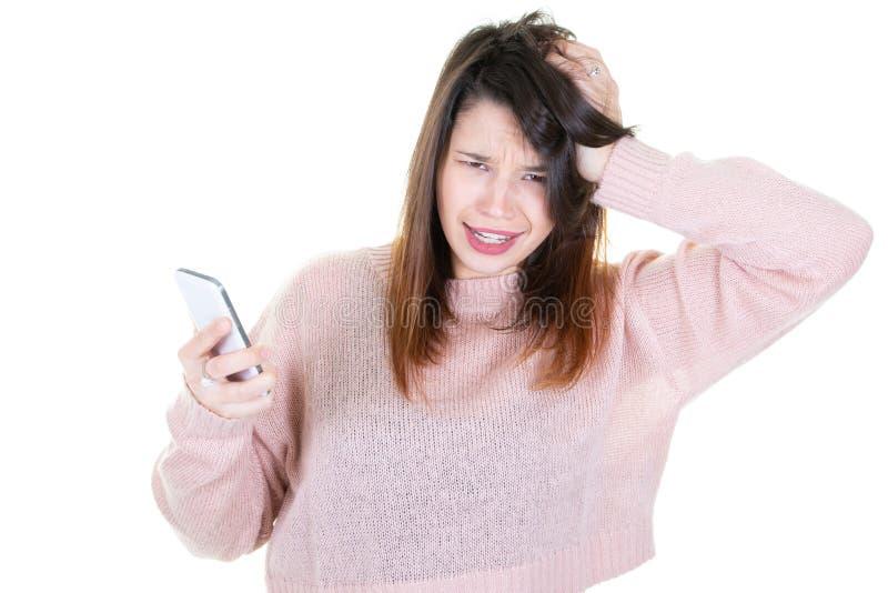Emotionellt stirra för ung kvinna på hennes mobiltelefon på vit bakgrund royaltyfri fotografi