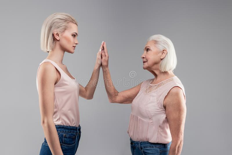 Emotionless siwowłosej starej kobiety złączona ręka z interesującą dziewczyną fotografia royalty free