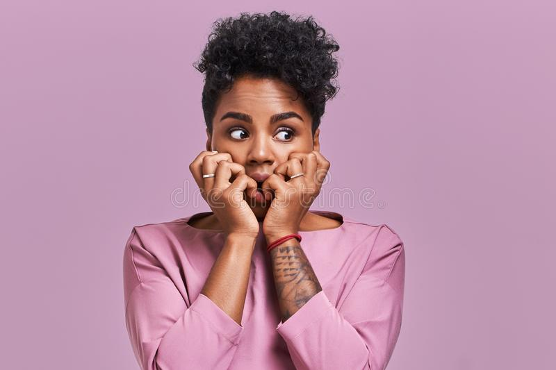 Emotions concept. Nervous emotional scared young lovely African American female stares at camera and opens mouth widely royalty free stock photography