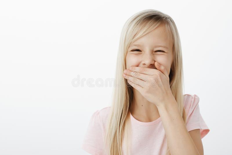 Emotive girl learnt funny word. Studio portrait of joyful adorable european kid with blond hair, covering mouth with stock photography