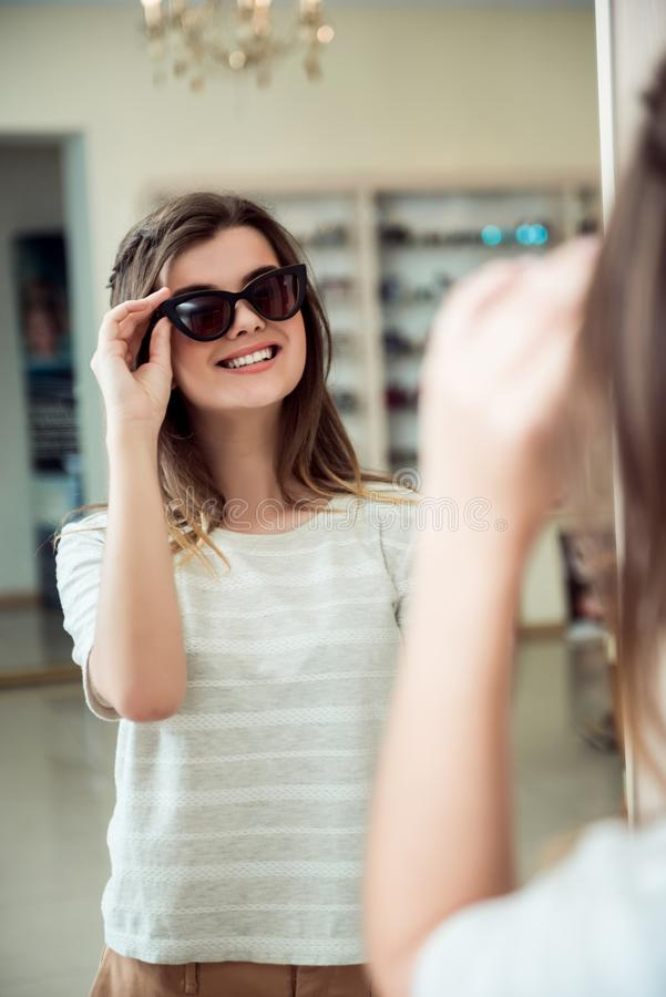 Emotive good-looking caucasian female student escapes from boredom and goes shopping in optician store, standing near royalty free stock photos