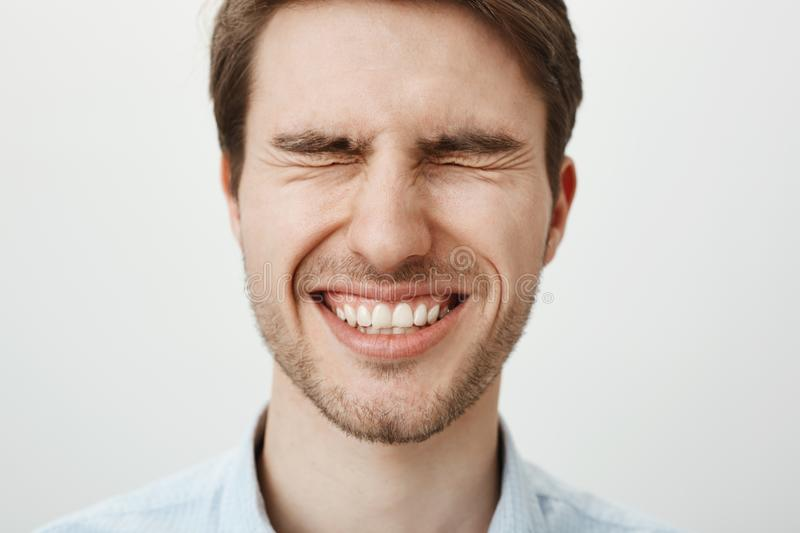 Emotive happy european guy with bristle standing with tightly closed eyes, squinting and smiling broadly, waiting for. Surprise or making wish near birthday stock photography