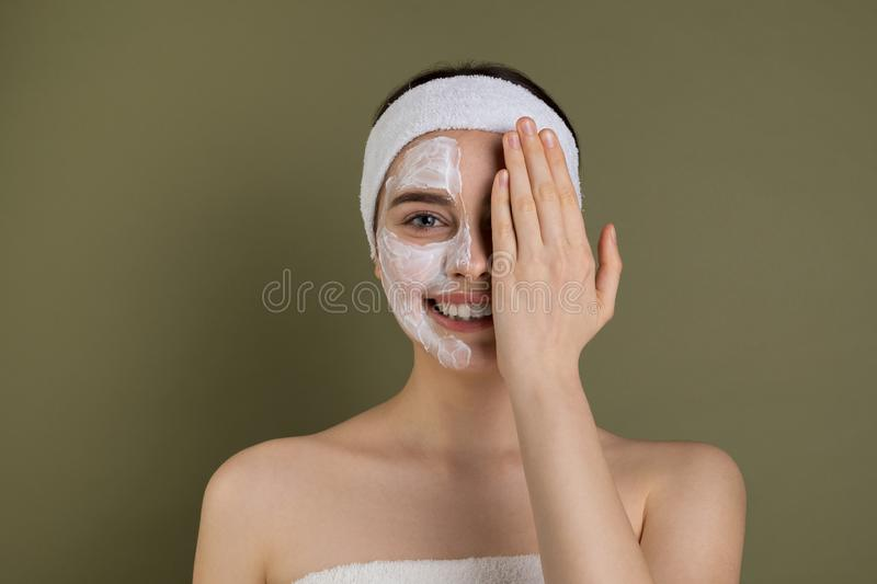 Emotive portrait of beautiful young woman with white mask bare shoulders. Having fun, clothing one eye with hand, pretty joyful girl looking at camera  on royalty free stock image