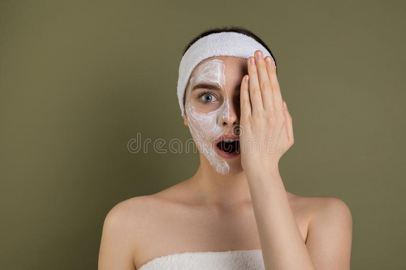 Emotive portrait of beautiful young woman with white mask bare shoulders. Having fun, clothing one eye with hand, pretty joyful girl looking at camera  on royalty free stock photography