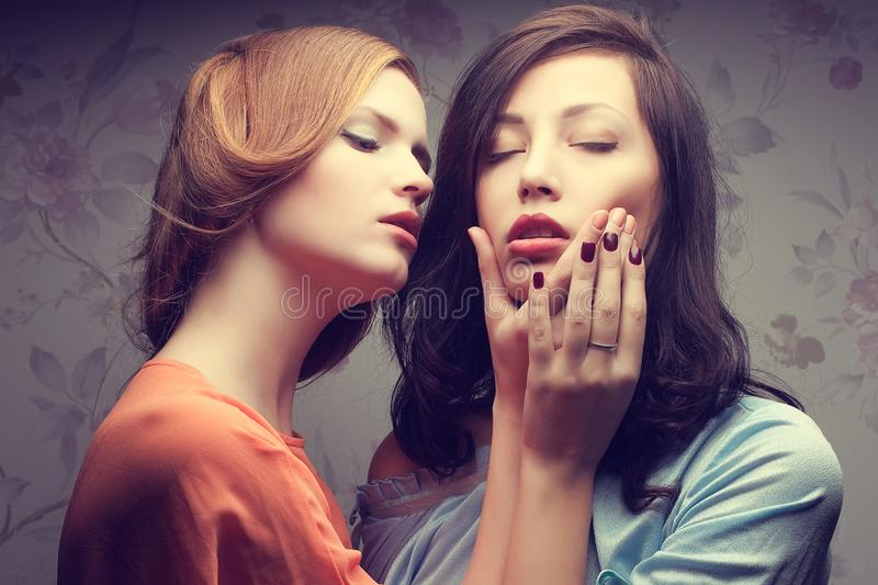 Emotive portrait of two gorgeous girlfriends in blue and orange stock photography