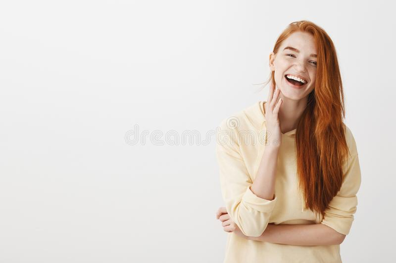 Emotive redhead girl grinning from happiness. Portrait of charming young european female with ginger hair feeling royalty free stock image
