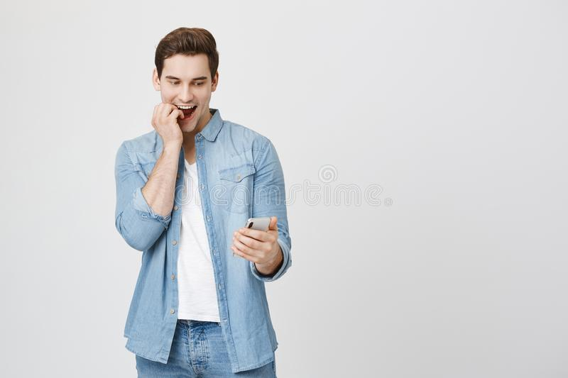 Emotive young cute student with surprised and amazed expression looking at smartphone biting fingers and smiling royalty free stock photos