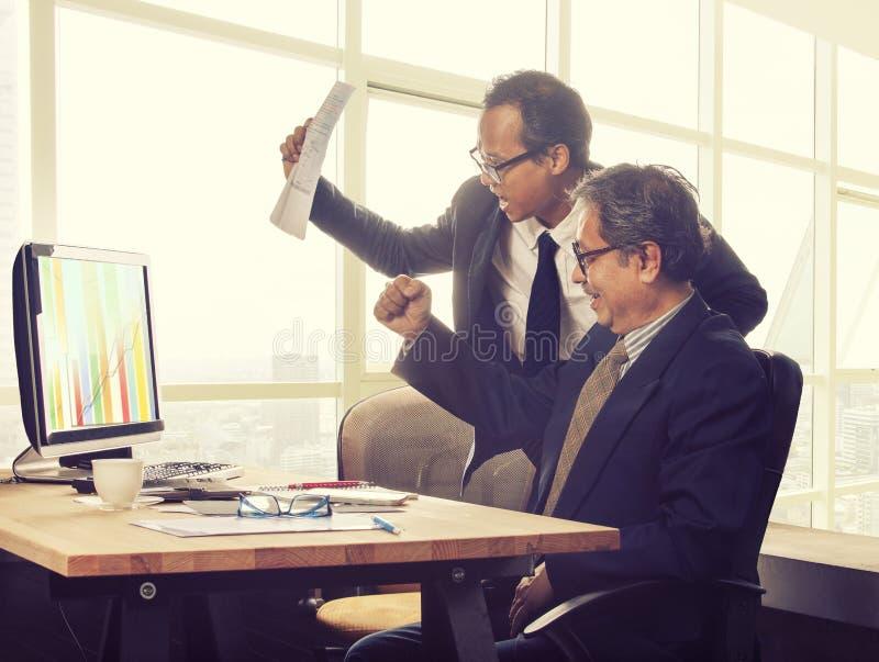 Emozione di felicità dell'uomo di affari di due asiatici che guarda al valore alto g immagini stock libere da diritti