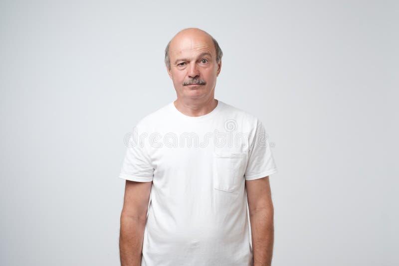 Emozioni anziane dell'uomo, ritratto dell'uomo caucasico senior serio che esamina macchina fotografica contro la parete grigia immagini stock libere da diritti