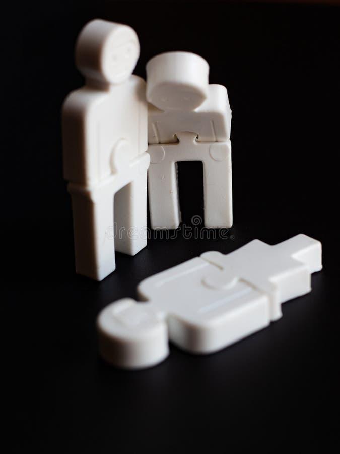 Emozioni del rammarico fra la gente, il concetto di supporto sociale, piccoli uomini del giocattolo su un fondo scuro fotografia stock