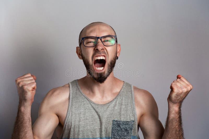 Emozioni di rabbia e dell'indignazione L'uomo in vetri ha serrato le sue mani nei pugni e gridate Il concetto di opposizione e immagini stock libere da diritti