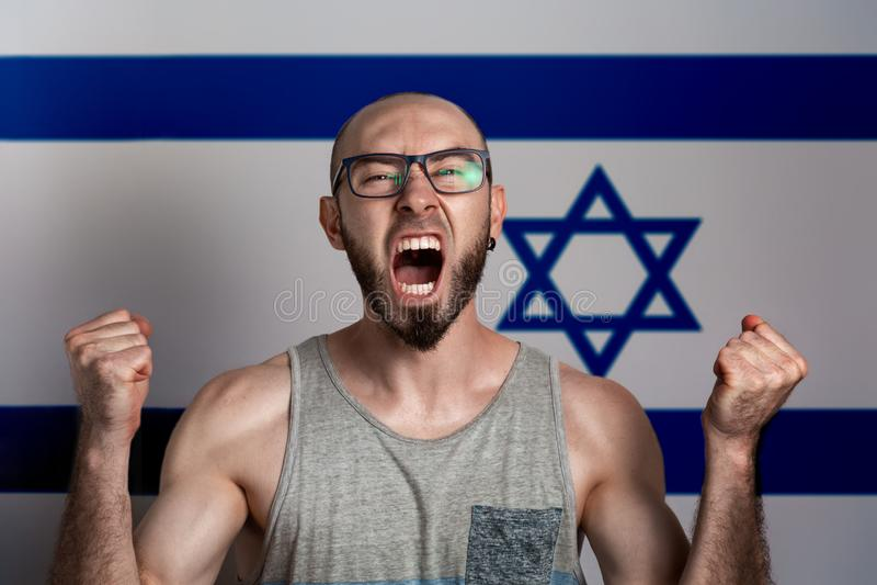 Emozioni di rabbia e dell'indignazione L'uomo in vetri ha serrato le sue mani nei pugni e gridate Nei precedenti è la bandiera di immagine stock