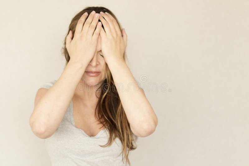 emozioni Emicrania di wis della giovane donna su un fondo grigio Copi lo spazio Ragazza spiacente e turbata fotografia stock libera da diritti