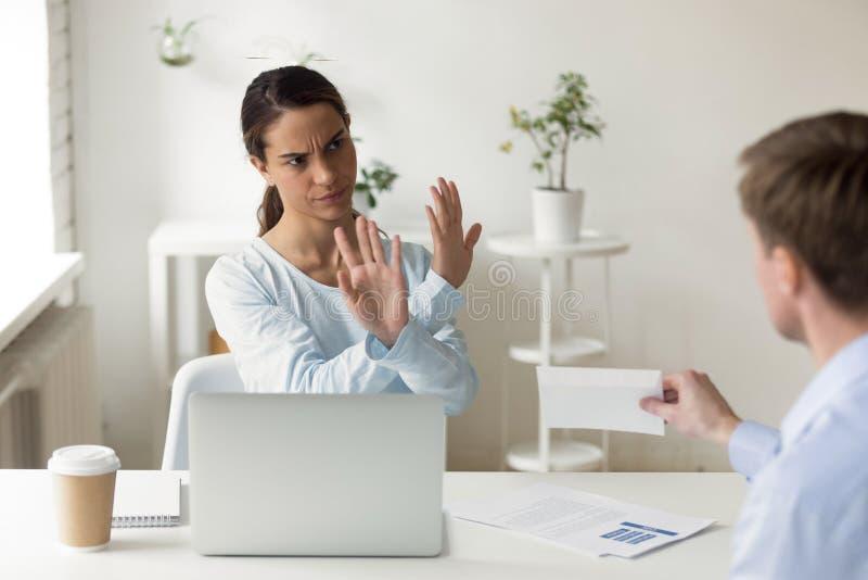 Empörte Geschäftsfrau, die Umschlag mit Bestechungsgeld am Arbeitsplatz ablehnt lizenzfreie stockfotografie