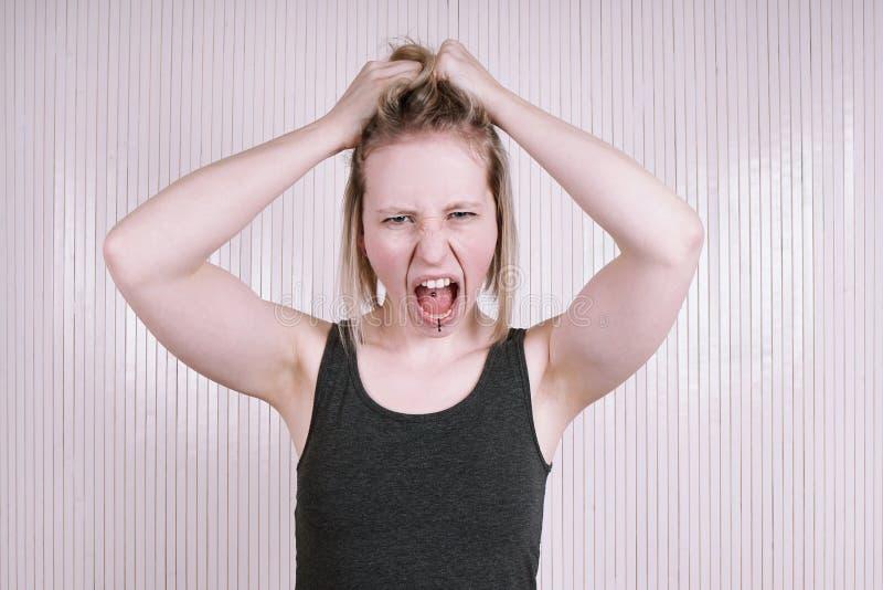 Empörte junge Frau, die einen schreienden und schreienden Temperamentwutanfall hat lizenzfreie stockfotografie