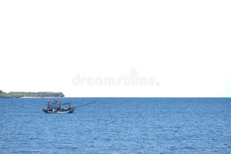 Empañó una navegación del barco de pesca en un mar azul profundo con el fondo blanco del cielo fotografía de archivo