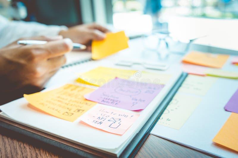 Empañe al hombre de negocios que trabaja con el papel de nota para inspirarse ideas imagen de archivo libre de regalías