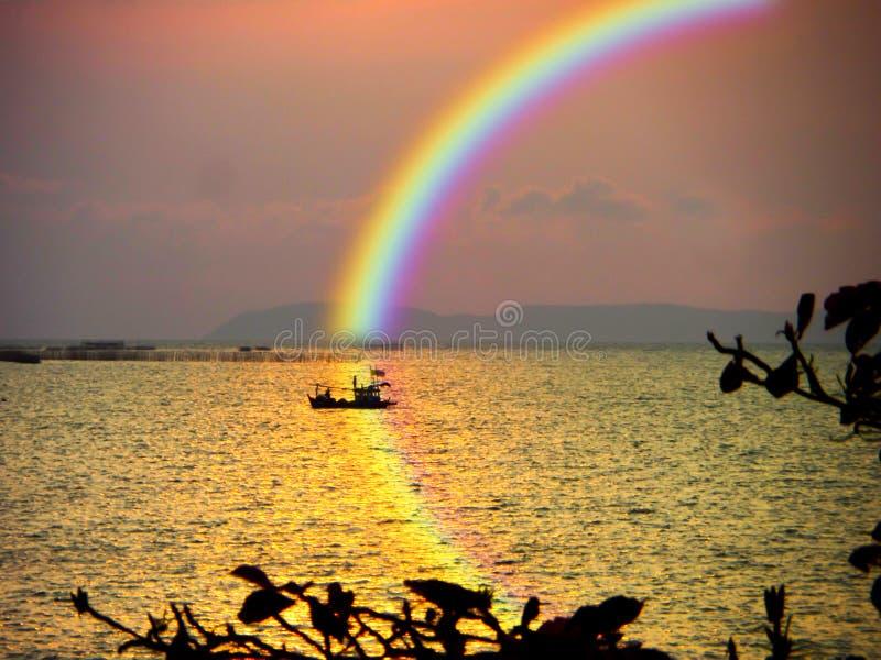 empañe el barco en arco iris de reflexión del cielo del arco iris de la puesta del sol del mar en el agua imagenes de archivo