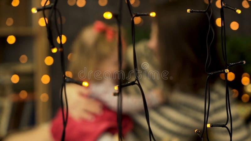 Empañe el retrato de la madre feliz y del bebé adorable detrás de las guirnaldas amarillas en el cuarto adornado con las ramas ve fotografía de archivo libre de regalías