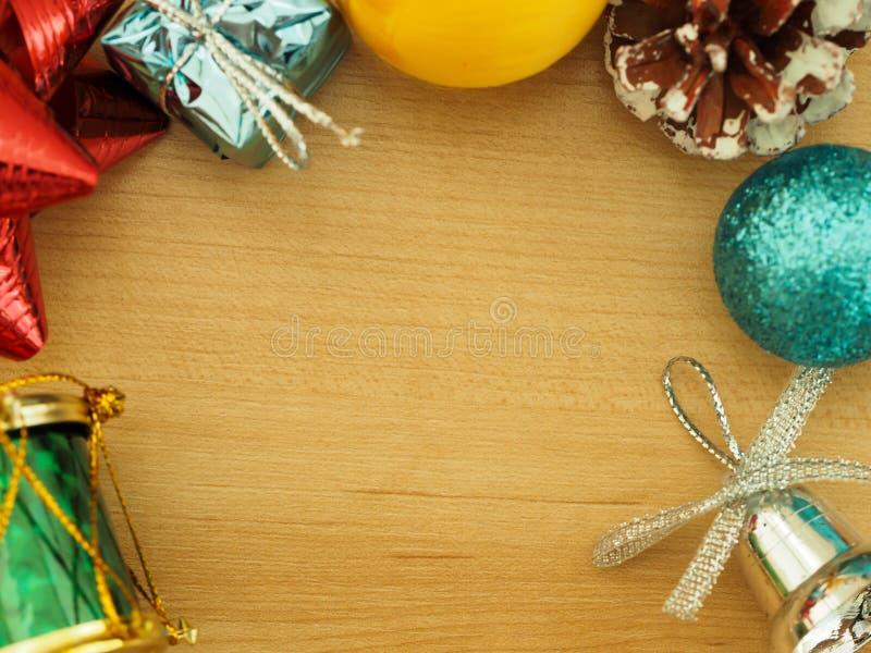 Empañe las decoraciones de la Navidad en el piso de madera con el espacio para el texto en el centro imágenes de archivo libres de regalías