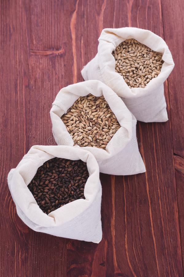 Empalideça, o caramelo, malte do chocolate no sacos Fabricação de cerveja de cerveja do ofício de fotos de stock