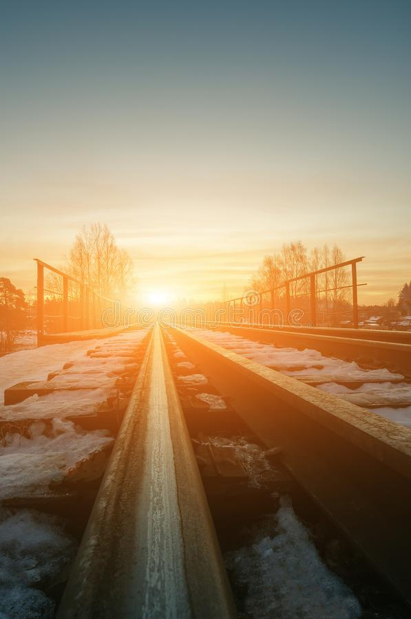 Empalme de la vía de ferrocarriles en la estación de trenes contra la luz hermosa del uso del cielo del sistema del sol para la t foto de archivo libre de regalías