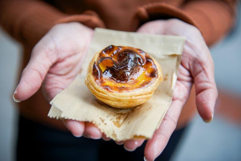 Empanada agria de las natillas del huevo dulce en la mano del ` s de la mujer fotografía de archivo