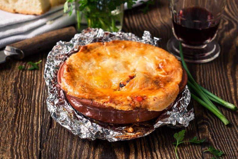 Empanada caliente jugosa de la carne en un pote de cerámica del horno imagen de archivo libre de regalías