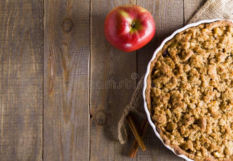Empanada con la migaja en fondo del tablón Apple desmenuza Empanada de Apple con la migaja en fondo de madera fotografía de archivo libre de regalías
