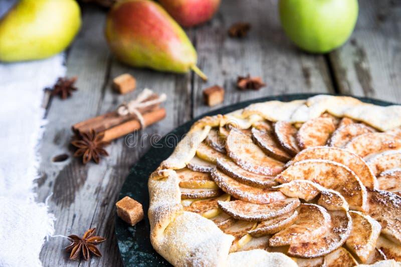 Empanada con las manzanas, las peras y el canela en un viejo fondo de madera fotografía de archivo libre de regalías